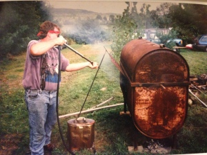 This is my dad keeping the temperature of the oil tank under control.  There's a whole pig in there!  It fed about 40 people.
